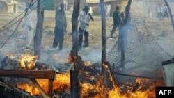Суданцы наблюдают последствия бобардировки рынка правительственными ВВС.