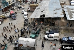 FILE - Rescue workers and army soldiers gather at the site of a blast at a vegetable market in Quetta, Pakistan, April 12, 2019.