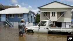 ຜູ້ຊາຍຄົນນຶ່ງ ຢຶນເບິ່ງລົດ ທີ່ຈອດໃນຖະໜົນທີ່ຖືກນໍ້າຖ້ວມ ຢູ່ເຂດ Breakfast Creek ຊານເມືອງຂອງນະຄອນ Brisbane (12 ມັງກອນ 2011)