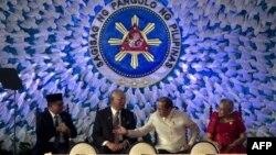 摩洛伊斯兰解放阵线主席穆拉德•易卜拉欣(左)、马来西亚总理纳吉布•拉扎克(左二)、菲律宾总统本尼诺•阿基诺(右二)和总统顾问特雷西塔•金托斯-戴雷斯(右)在马尼拉签署《关于邦萨摩洛的全面协议》之前交谈。(2014年3月27日)