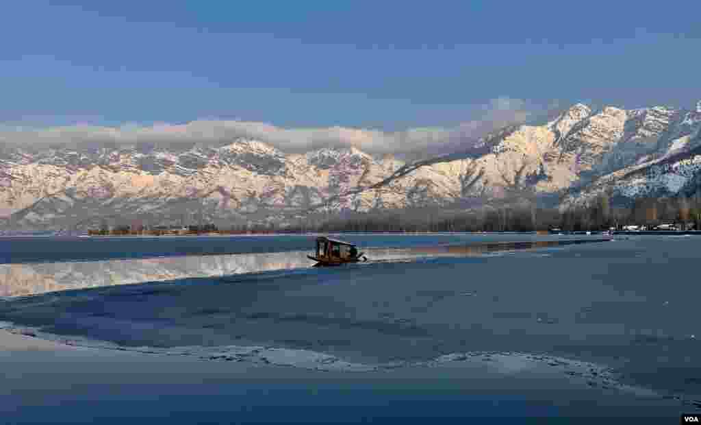 ڈل جھیل کے اطراف پہاڑوں کی چوٹیوں پر بھی برف کی حکمرانی ہے جب کہ ایک کشتی جھیل کے برفیلے پانی میں رواں دواں ہے۔