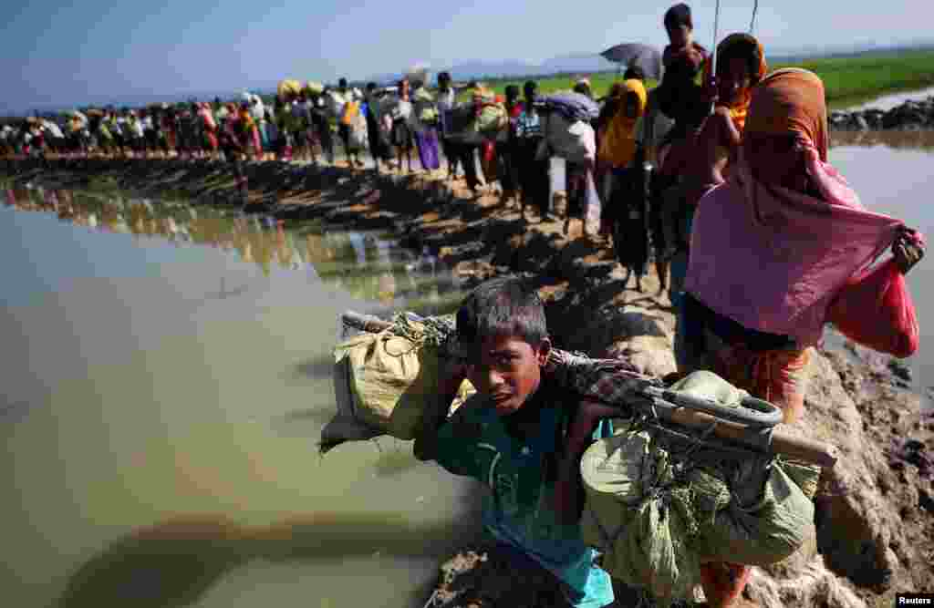 Rohingya refugees make their way to a refugee camp after crossing the Bangladesh-Myanmar border in Palong Khali, near Cox's Bazar, Bangladesh.