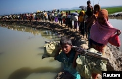 FILE - Rohingya refugees make their way to a refugee camp after crossing the Bangladesh-Myanmar border in Palong Khali, near Cox's Bazar, Bangladesh, Nov. 3, 2017.