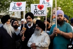 FILE _ Members of the Manchester Sikh Community attend a vigil in Albert Square, Manchester, England, May 23, 2017, the day after the suicide attack at an Ariana Grande concert that left 22 people dead as it ended on Monday night.