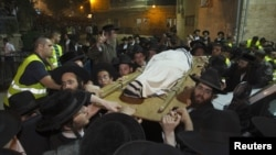 Warga Yahudi Ultra-Orthodox mengangkat jenazah Rabbi Yosef Shalom Elyashiv menuju sinagog sebelum dimakamkan di wilayah Mea Shearim, Yerusalem (18/7).