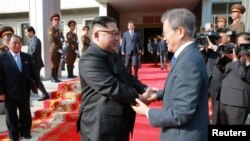 FILE - South Korean President Moon Jae-in shakes hands with North Korean leader Kim Jong Un during their summit at the truce village of Panmunjom, North Korea, May 27, 2018. (Handout photo from KCNA via Reuters)