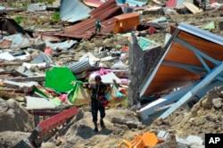 Čovek nosi stvari koje je izvukao iz ruševina, nakon što su snažan zemljotres i cunami pogodili Palu, Celtrana Suavesi, Indonezija, 1. oktobra 2018.