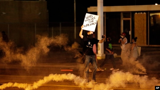 A protester stands in the street after police fired tear gas to disperse a crowd Sunday, Aug. 17, 2014, during a protest for Michael Brown, who was killed by a police officer in Ferguson, Missouri.