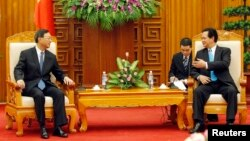Chinese State Councilor Yang Jiechi (L) listens to Vietnamese Prime Minister Nguyen Tan Dung in Hanoi, June 18, 2014.