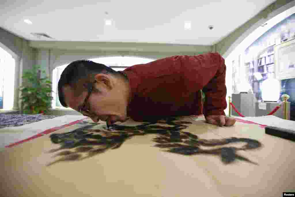 Seniman Han Xiaoming melukis dengan menggunakan lidahnya di Hangzhou, Zhejiang, China.