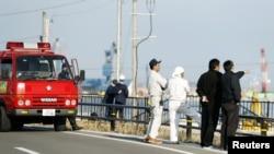 救火队员和福岛当地居民在海啸预警之后观察海水水位(2016年11月22日)