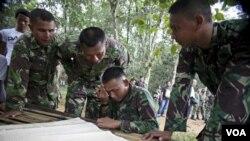 Para anggota Tim SAR mempelajari peta lokasi jatuhnya pesawat di CASA 212 Bahorok, Sumatera Utara. Evakuasi baru dilakukan Jumat pagi mengingat medan yang cukup sulit.