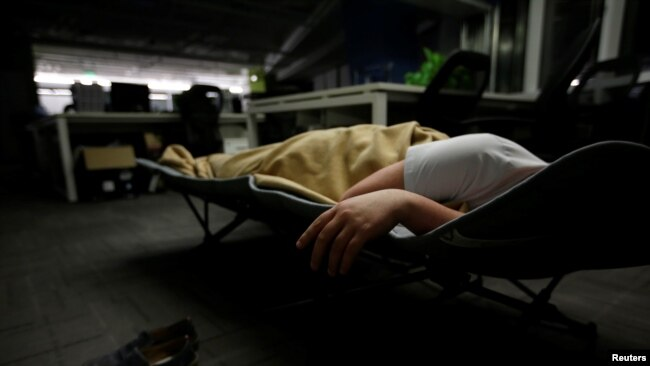 A system engineer at RenRen Credit Management Co., sleeps on a camp bed at the office
