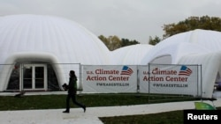 A woman walks past a tent, set up by U.S. groups opposed to U.S. President Donald Trump climate policies, on the sidelines of U.N. COP-23 climate conference in Bonn, Germany, Nov. 9, 2017. According to the State Department, the U.S. is represented at the talks.