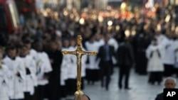 人们在伯利恒圣诞教堂外的圣诞庆祝活动中举着十字架。(2012年12月24日)