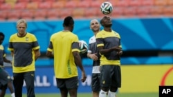 FILE - Cameroon's Pierre Webo, right, controls a ball during an official training session at the Arena da Amazonia in Manaus, Brazil, June 17, 2014. Many African youngsters dreaming of becoming wealthy football stars abroad face an uphill battle, a new report finds.