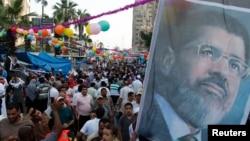 穆尔西的支持者8月8日在阿比亚清真寺外举着穆尔西的肖像举行抗议活动。