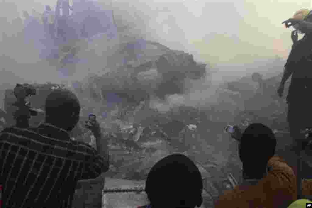People use their mobile phones to take photos of the wreckage of a Dana Airlines plane crash in Lagos, Nigeria, Sunday, June 3, 2012.