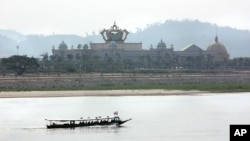 A boat on the Mekong River passes Chinese-run Kings Roman Casino in the special economic zone in Laos. (D. Schearf/VOA)