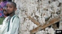 Bé trai Endashew và em gái Yeshiwork, mất cả cha lẫn mẹ vì HIV/AIDS ngồi trước căn nhà ở gần thủ đô Addis Ababa, Ethiopia