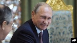 Russian President Vladimir Putin smiles as he listens to Russia's Foreign Minister Sergey Lavrov, left, at the meeting of the Collective Security Treaty Organization (CSTO) in Dushanbe, Tajikistan, Tuesday, Sept. 15, 2015.