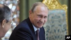 ປ. ຣັດເຊຍ ທ່ານ Vladimir Putin ນັ່ງຍິ້ມ ໃນຂະນະທີ່ໂອ້ລົມ ກັບລັດຖະມົນຕີການຕ່າງປະເທດ ທ່ານ Sergey Lavrov, ຊ້າຍ, ໃນກອງປະຊຸມດ້ານຄວາມປອດໄພ ຂອງພາກພື້ນ ຫຼື (CSTO) ທີ່ Dushanbe, Tajikistan, 15 ກັນຍາ, 2015.