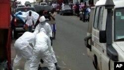 Des travailleurs de la santé, aidant une victime du virus à Ebola (AP)