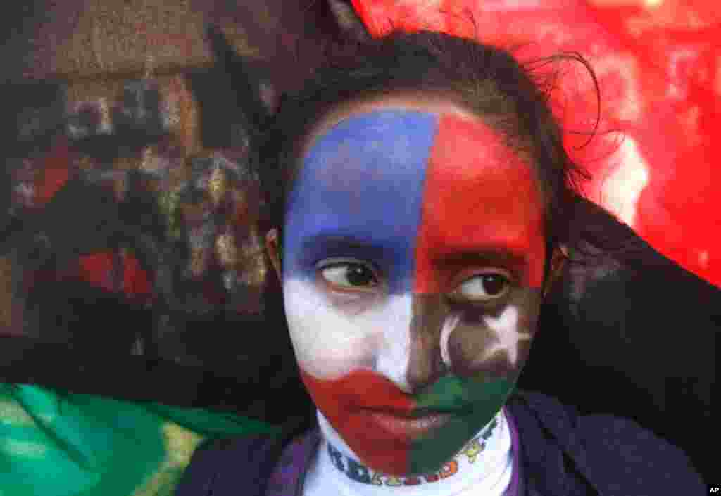 French and Kingdom of Libya flags are painted on the face of a protester during a demonstration in support of air strikes in Libya, in Benghazi. (Reuters)