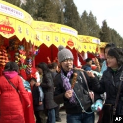 Chinese visitors enjoy snacks at this year's Spring Festival fair at the Yuanming Yuan park