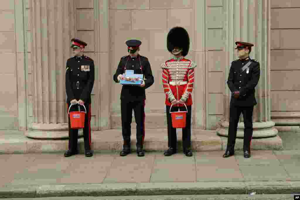 Members of the British military's Honorable Artillery Company collect donations for the annual poppy appeal ahead of Armistice Day outside the Bank of England in the City of London.