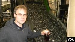 CEO perusahaan JBI, Inc., John Bordynuik, memegang setoples bahan bakar yang diproduksi dari limbah plastik. (VOA/D. Robison)