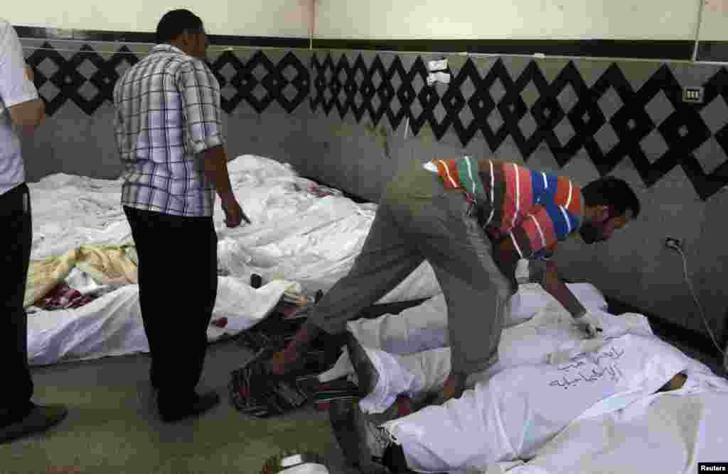 Men try to identify bodies of protesters killed in clashes between Mursi supporters and police in Cairo's Nasr city July 27, 2013.