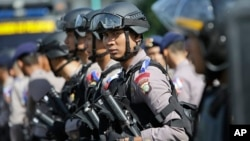 Indonesian police officers deploy with their riot gear in Jakarta, Indonesia, Dec. 23, 2015.