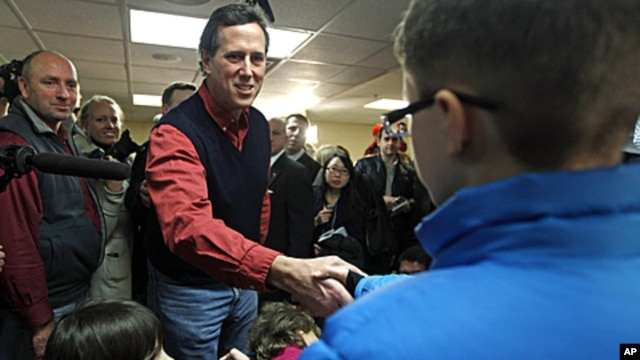 Republican presidential candidate former Pennsylvania Senator Rick Santorum reaches to greet children during a campaign stop in Brentwood, New Hampshire, January 4, 2012.