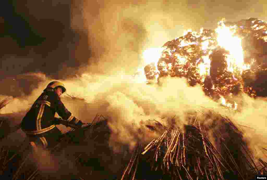 A firefighter attempts to extinguish a fire which broke out on piles of reed at a paper factory in Changde, Hunan province, China, Feb. 16, 2014.