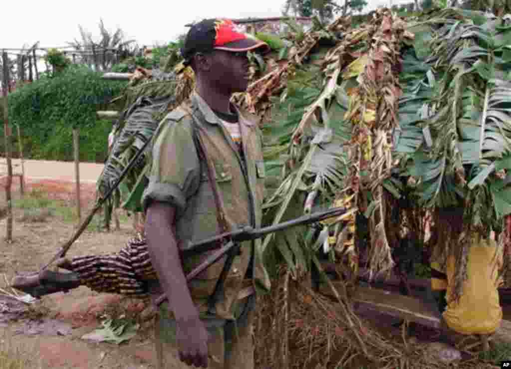 An unidentified Rwandan rebel carries a machine gun some 20 kilometers from the town of Masisi, Democratic Republic of Congo on Friday, Nov. 4, 2005. The Rwandans shopping in a Congolese market say they want to live peacefully alongside Congolese villager