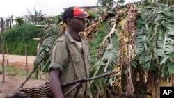 Un rebelle non identifié porte une mitrailleuse à environ 20 kilomètres de Masisi, RDC, 4 novembre 2005.