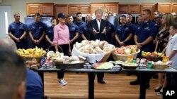 El presidente Trump y la primera dama, Melania Trump (blusa rosada) celebran Thanksgiving con miembros de la Guardia Costera en Florida.