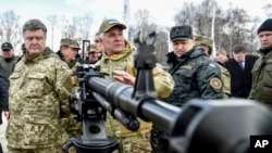 FILE - Ukraine's President Petro Poroshenko, left, followed by officials, listens to a weapons expert as he inspects weapon systems for the Ukrainian Army at a military base in Novi Petrivtsi outside Kiev, Ukraine, April 4, 2015.