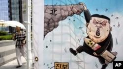 지난 1일 서울에서 북한 인권 개선을 요구하며 열린 집회에 등장한 포스터. 핵무기를 든 김정은 제1위원장이 벼랑 끝에 매달려있다.