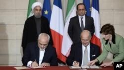 Presiden Iran Hassan Rouhani dan Presiden Perancis Francois Hollande menyaksikan kesepakatan bilateral antara Iran-Perancis yang ditandatangai Menlu Javad Zarif (kiri) dan Laurent Fabius di Paris (foto: dok). Bank-bank internasional masih enggan mendanai kesepakatan bisnis dengan Iran pasca dicabutnya sanksi ekonomi.