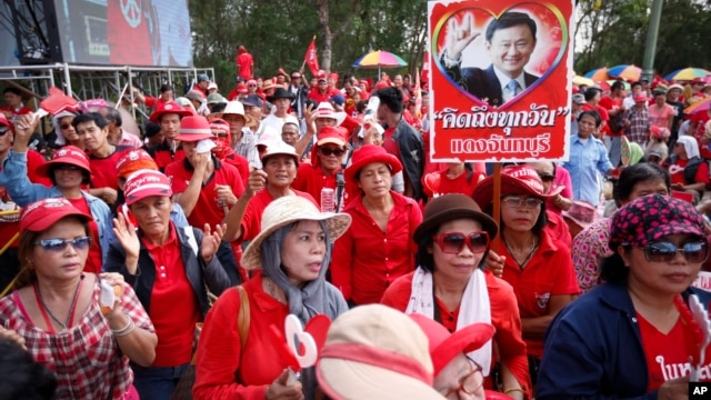 Pro-government protesters show a portrait of former Prime Minister Thaksin Shinawatra during a rally in Aksa, outskirt of  Bangkok, Thailand, Saturday, May 10, 2014.