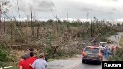Warga setempat mengamati pembersihan puing-puing di sepanjang jalan pasca tornado di Beauregard, Alabama, AS dalam 3 Maret 2019. (Foto: videograb/Scott Fillmer via Reuters)