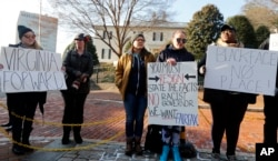 Demonstrators hold signs and chant outside the Governor's Mansion in Richmond, Va., Feb. 2, 2019. The demonstrators were calling for the resignation of Virginia Gov Ralph Northam after a decades-old, racially insensitive photo from his medical school yearbook page was widely distributed Friday.