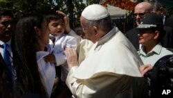 Pope Francis greets the child of an inmate at the San Joaquin women's prison in Santiago, Chile, Jan.16, 2018.
