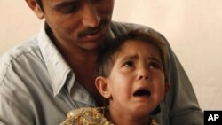 FILE - Parvez holds his 3-year-old daughter Sunam, who is dressed in the outfit she wore for the party in which she was engaged to her seven-year-old cousin, Nieem, in Kabul, Afghanistan, July 11, 2007.