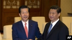 中共总书记习近平(右)星期五在北京人民大会堂会晤了访华的日本首相安倍晋三的特使山口那津男