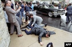 Esta foto puesta a disposición por la Biblioteca y Museo Presidencial Ronald Reagan muestra al secretario de Prensa de la Casa Blanca, James Brady, y al oficial de policía Thomas Delahanty, heridos en el suelo frente al Washington Hilton.