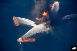 FILE - The Deepwater Horizon oil rig burns in the Gulf of Mexico following an explosion that killed 11 workers and caused the worst offshore oil spill in the nation's history, April 21, 2010.