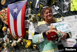 FILE - Maria Perdomo grieves by a makeshift memorial for the victims of the Surfside's Champlain Towers South condominium collapse in Miami, Florida, July 8, 2021.